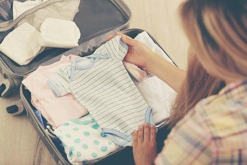 Mama pakująca ubrania dla noworodków na lato do walizki