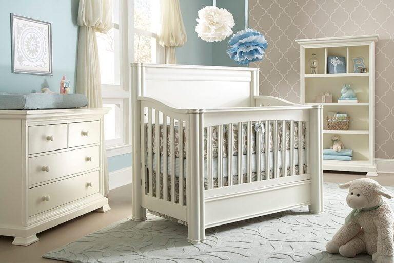 Łóżeczko dla dziecka stojące na środku biało-niebieskiego pokoju