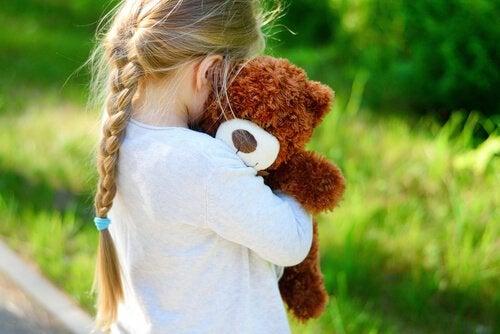 Stojąca tyłem dziewczynka przytulająca misia