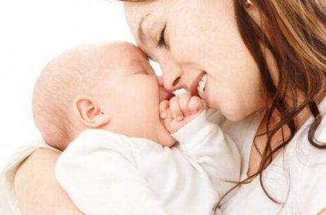Uśmiechnięta mama dotykająca czołem czoła niemowlęcia
