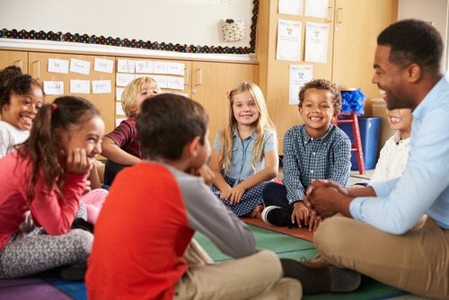 Dzieci z nauczycielem siedzący w kole na podłodze