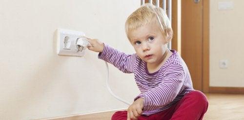 Dziecko bawi się gniazdkiem elektrycznym