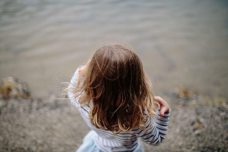 Dziewczynka o brązowych włosach stojąca nad wodą