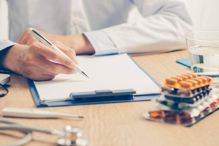 Lekarz piszący na kartce, na pierwszym planie leki