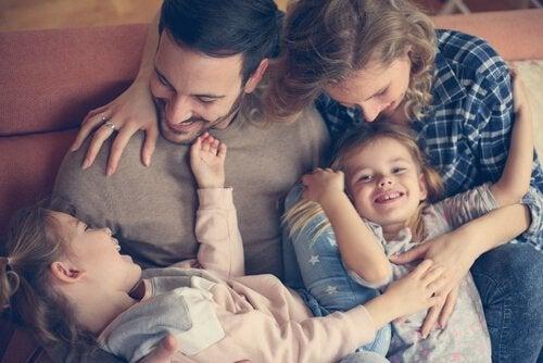 Przytulający się i roześmiani mama, tata i dwie córki - powody do radości w ciąży i wyrzeczenia