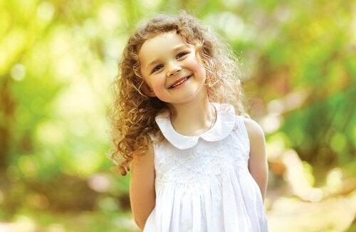 Uśmiechnięta blond dziewczynka z kręconymi włosami