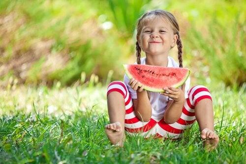 Uśmiechnięta dziewczynka siedząca na łące i jedząca arbiza
