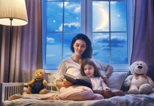 Mama czytająca bajkę na dobranoc swojej córce