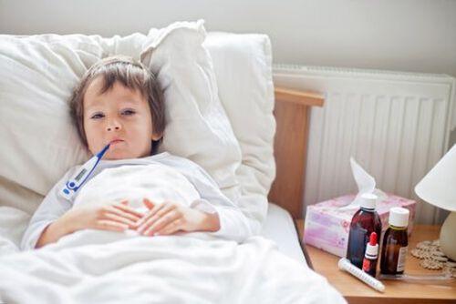 Chłopiec z gorączką leży w łóżku