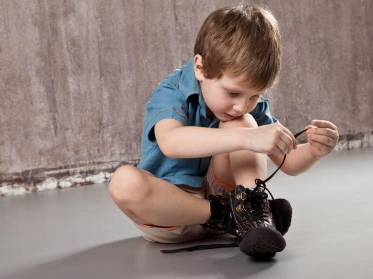 Chłopiec siedzący na podłodze i wiążący buty