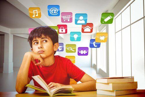 Chłopiec siedzący nad książką otoczony kolorowymi ikonami jak z komputera