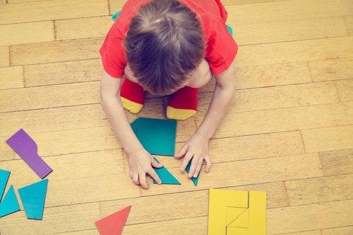 Chłopiec układający na podłodze figury z pociętych kolorowych kartek - ćwiczenia na koncentrację dla dzieci