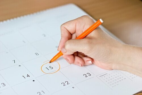 Dłoń kobiety zaznaczająca kółkiem dzień w kalendarzu - opóźniony poród i jego przyczyny