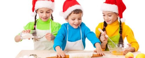 Trzy dziewczynki i chlopiec w czapkach mikołaja robiący ciasteczka - Świąteczne zajęcia dla rodziny