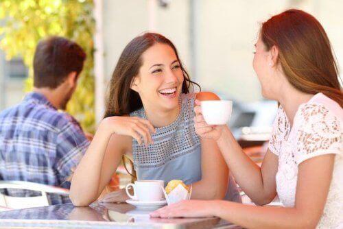 Dwie śmiejące się kobiety siedzące przy stoliku w kawiarni