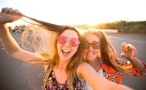 Dwie uśmiechnięte nastolatki w okularach przeciwsłonecznych robiące sobie selfie