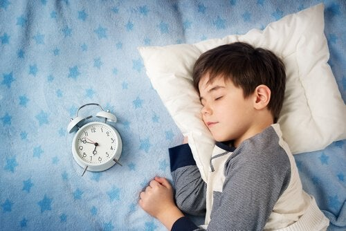 Chłopiec, który śpi obok budzika