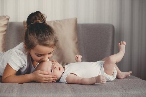 Dziewczynka całująca niemowlę leżące na kanapie w główkę