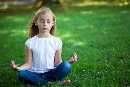 Dziewczynka medytuje na trawie