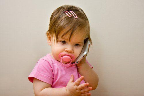 Dziewczynka rozmawia przez zabawkowy telefon