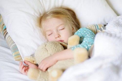 Śpiąca dziewczynka przytulająca misia