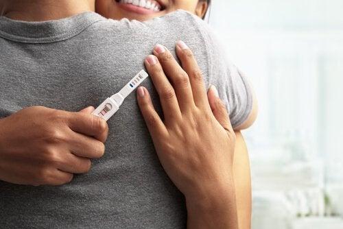 Kobieta trzymająca w dłoni test ciążowy i przytulająca mężczyznę - najlepsza pora roku na zajście w ciążę