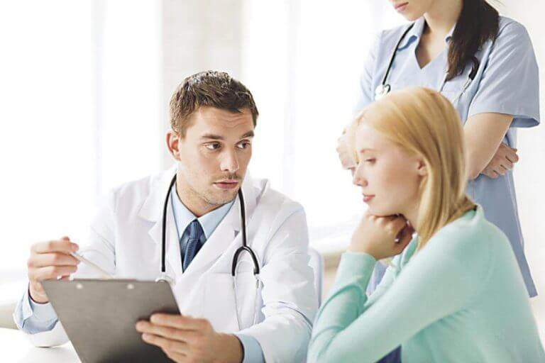 Lekarz i pielęgniarka pokazujący pacjentce wyniki badań