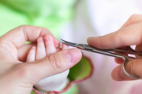 Mama obcinająca paznokcie niemowlęciu