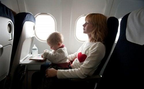 Mama z dzieckiem na kolanach lecących samolotem - podróżowanie z niemowlakiem