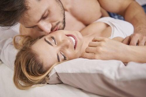 Mężczyzna całujący kobietę w łóżku - seks po porodzie
