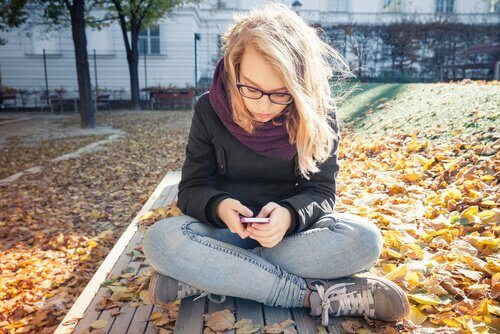 Nastolatka siedząca po turecku na ławce w jesiennym parku, pisząca na telefonie