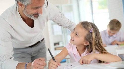 Nauczyciel pochylający się z uśmiechem nad dziewczynką siedzącą w ławce