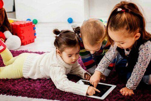 Pokolenie alfa - dzieci na dywanie bawią się tabletem