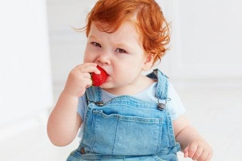 Rude dziecko w ogrodniczkach jedzące truskawkę