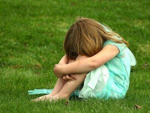 Smutne dziecko siedzi skulone na trawie