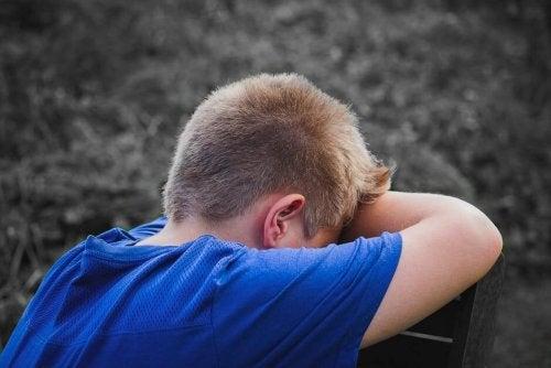 Smutny chłopiec opierający głowę na rękach założonych na krzesło