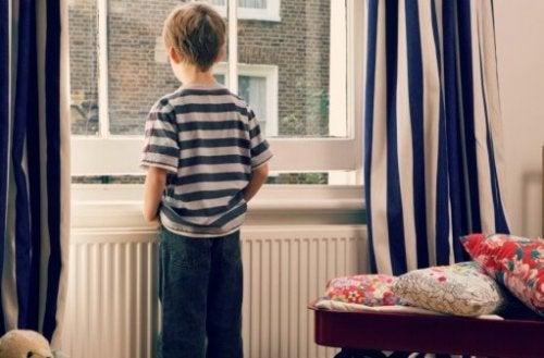 Smutny chłopiec stojący przed oknem