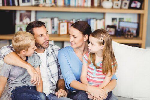 Mama i tata siedzący z synem i córką na kanapie i prowadzący dyskusję