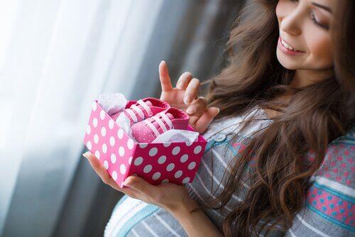 Uśmiechnięta kobieta w ciąży patrząca na buciki dziecięce w pudełku