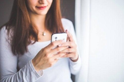 Uśmiechnięta kobieta wpatrzona w ekran telefonu