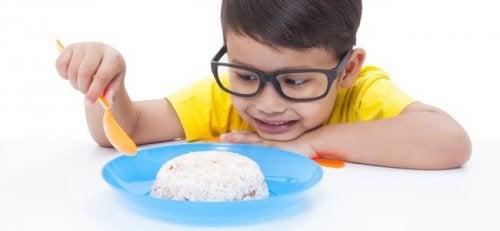 Uśmiechnięty chłopiec w okularach jedzący łyżką ryż