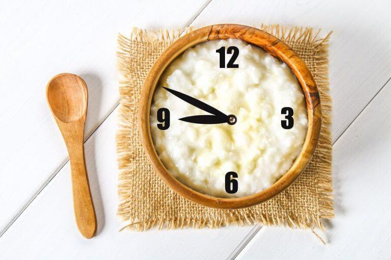 Zegar na misce z ryżem i leżąca obok łyżka