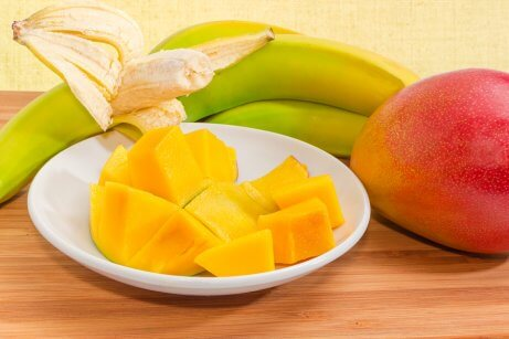 Banan i jabłko pokrojone na talerzu
