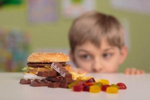 Chłopiec patrzący zza stołu na słodycze
