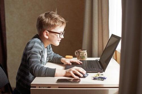 Chłopiec wpatrzony w komputer