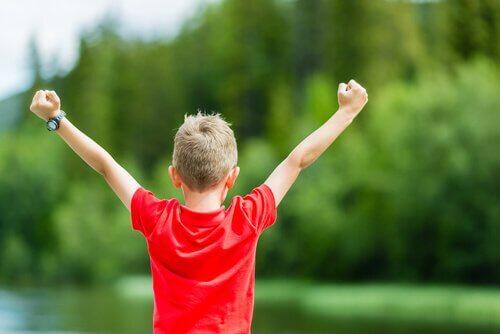 Chłopiec rozkłada ręce w geście zwycięstwa