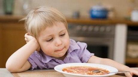 Dziecko opierające głowę na ręce, patrzące na zupę - dziecko nie chce jeść