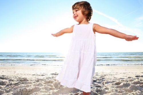 Dziewczynka w białej sukience nad morzem