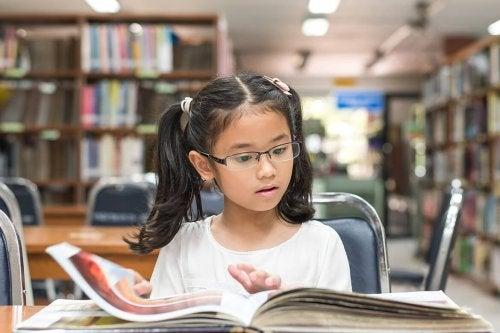 Dziewczynka w okularach czytająca w bibliotece - jak wspierać utalentowane dziecko