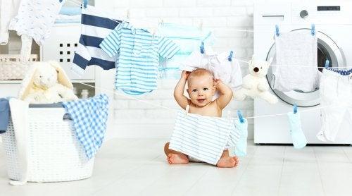 Niemowlak bawiący się ubraniami w pralni